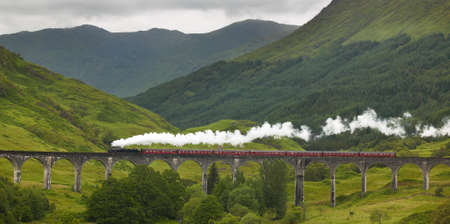 black train: Scottish steam train passing a classic bridge. Horizontal Stock Photo
