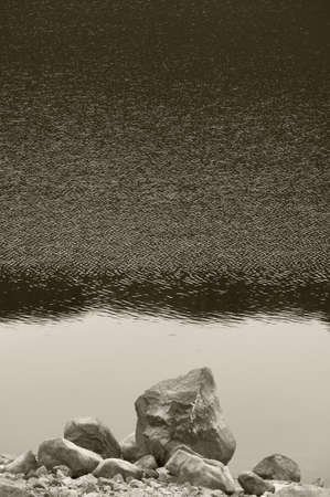 Scottish landscape with loch and rocks on a rainy day. Vertical photo