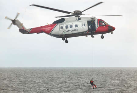 coastguard: Coastguard rescue helicopter team in action. Scotland. UK. Horizontal