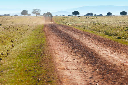 all weather: Dirty road in a mediterranean meadow with minibus. Cabaneros. Spain. Horizontal Stock Photo