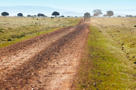 minibus: Dirty road in a mediterranean meadow with minibus. Cabaneros. Spain. Horizontal Stock Photo