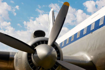aircraft rivets: Old aircraft propeller and airframe with blue sky background. Horizontal