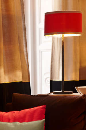 Home interior with red lamp and window with curtains. Vertical photo