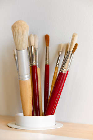 Different kinds of paintbrushes over a wooden table. Vertical photo