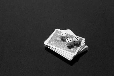 Poker cards and craps in a table game. Black and white