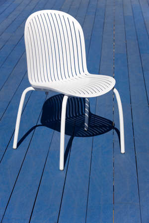 vertical format: White plastic chair over a blue wooden floor. Vertical format