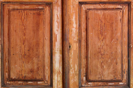 wasted: Antique and wasted wooden cabinet doors with metallic lock. Horizontal Stock Photo