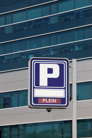 plein: Parking signpost with plein text and modern building