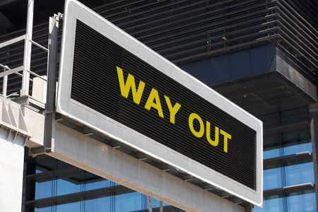 way out: Way out signpost in the city with building facade . Horizontal Stock Photo