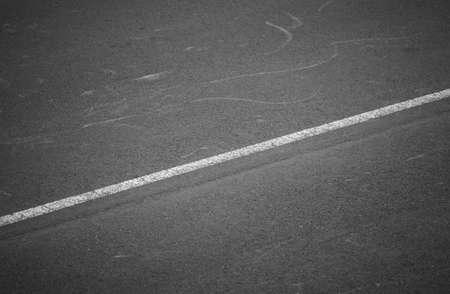 White line over an old asphalt street. Black and white. Horizontal Stock Photo