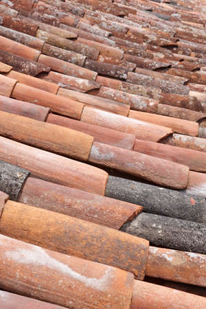 damaged roof: Old clay tile roof detail in vertical format. Warm tone