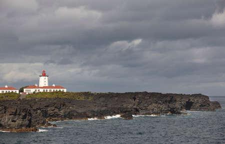 clody: Rocky coastline landscape with lighthouse in Pico. Ponta da Ilha. Portugal