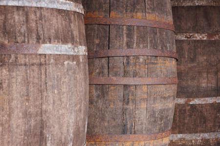 casks: Old wine wooden barrels detail in a winery. Warm tone. Horizontal