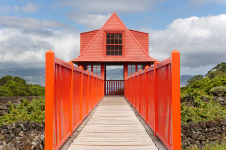 agriculture azores: Red wooden viewpoint pathway in Pico island vineyard. Azores. Portugal. Horizontal Stock Photo