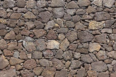 暖かいトーン玄武岩火山岩背景ファサード。水平方向 写真素材