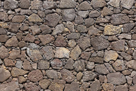 volcanic stones: Basalt volcanic rock background facade in warm tone. Horizontal