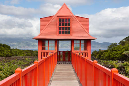 red sky: Red wooden viewpoint pathway in Pico island vineyard. Azores. Portugal. Horizontal Stock Photo