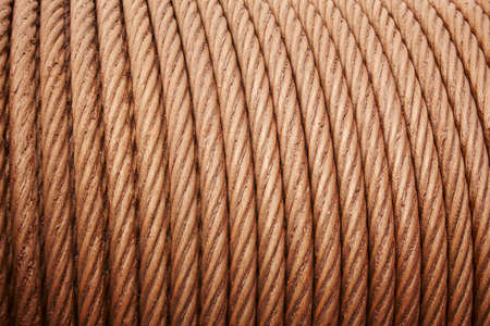 greased: Heavy steel coiled greased cable detail in warm tone. Horizontal Stock Photo
