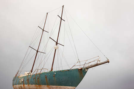 Rusty wooden sailboat waiting to be scraping in Azores. Portugal. Horizontal