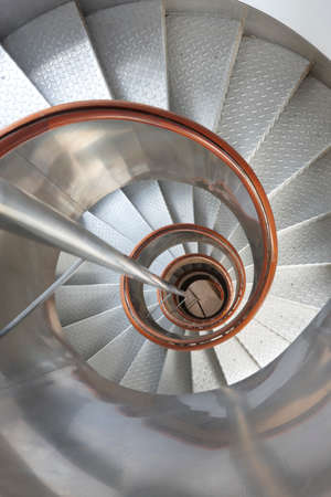 handrails: Metallic spiral stair with wooden handrails inside a lighthouse. Vertical Stock Photo
