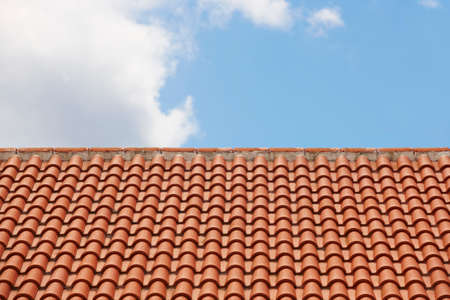 construction material: Orange tile roof over a blue sky. Horizontal format