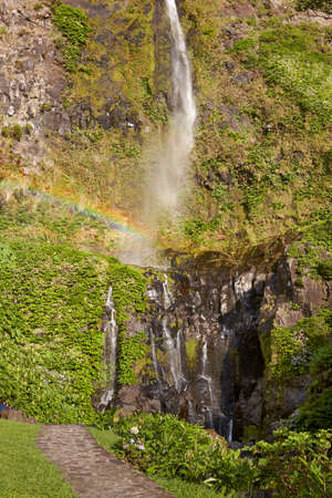 swimm: Waterfall and rainbow in Flores island, Azores. Poco do Bacalhau. Portugal
