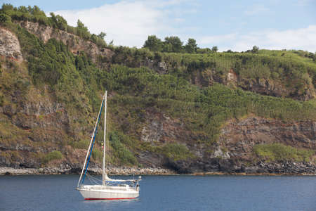 flores: Anchored sailboat in Flores island port entrance. Azores, Portugal. Horizontal