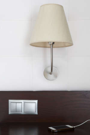 switches: Hotel room interior detail with lamp, switches and smartphone. Vertical