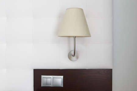 switches: Hotel room interior detail with lamp, switches and white wall. Horizontal