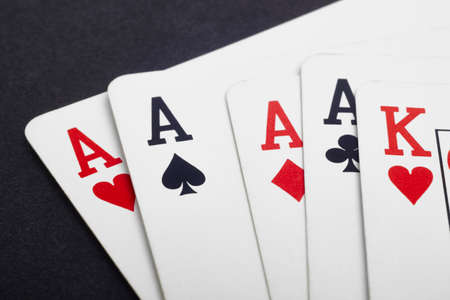 ace of spades: Poker card game with four aces and king. Black background. Horizontal Stock Photo