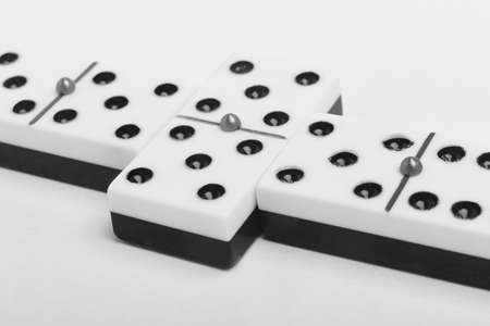 domino effect: Domino game with pieces over a white background. Black, white. Detail Stock Photo