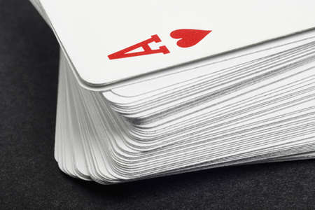 detail: Card game with ace of heart detail. Black background. Horizontal