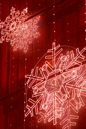 Christmas lights decoration on a building facade in red tone. Vertical