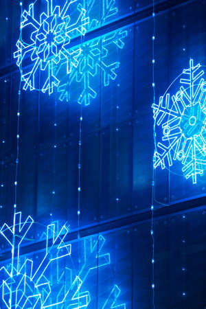 Christmas lights decoration on a building facade in blue tone. Vertical