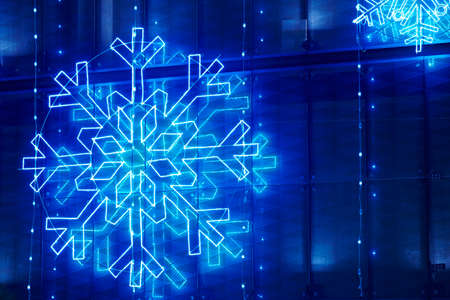 Christmas lights decoration on a building facade in blue tone. Horizontal