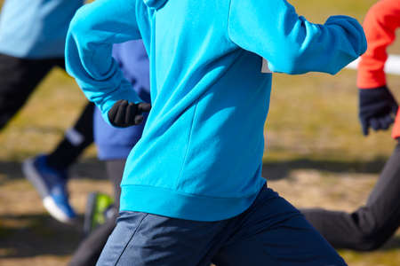 training session: Young athletics runners on a race. Outdoor circuit. Horizontal