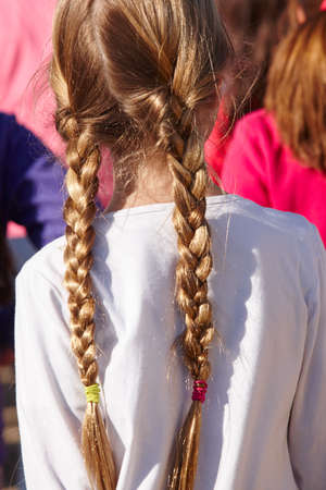 vertical format: Girl with pigtails on her back. Outdoors. Vertical format