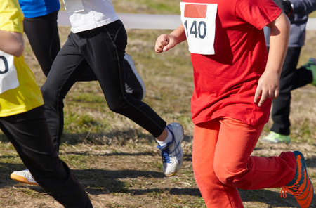 training session: Young athletic runners on a race. Outdoor circuit. Horizontal Stock Photo