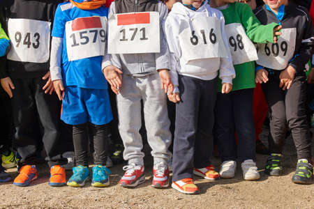 training session: Athletic children ready to start a cross country race. Outdoors. Horizontal Stock Photo