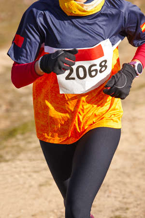 sport training: Female athletic runner on a cross country race. Outdoor circuit. Vertical Stock Photo