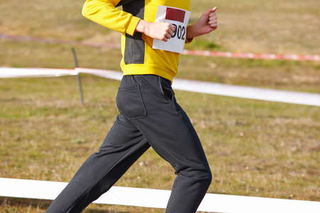 sport training: Junior athletic runner on a cross country race. Outdoor circuit. Horizontal