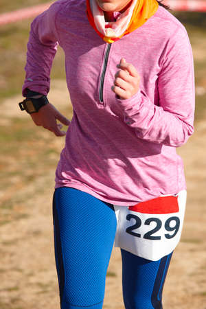 female athletic runner on a race outdoor circuit vertical stock