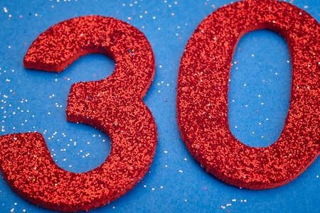 thirty: Number thirty red color over a blue background. Anniversary. Horizontal