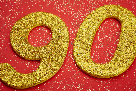 ninety: Number ninety golden color over a red background. Anniversary. Horizontal Stock Photo