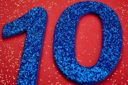 El número diez de color azul sobre un fondo rojo. Aniversario. Horizontal Foto de archivo - 53453175