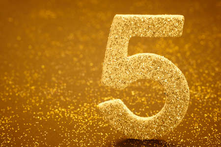 Number five golden color over a warm background. Anniversary. Horizontal