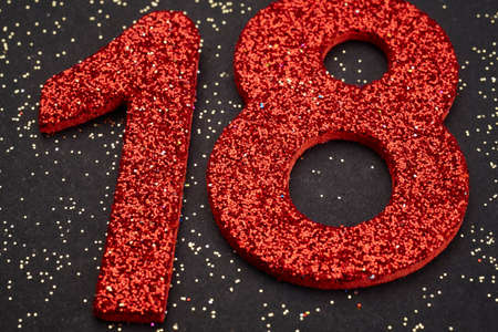 eighteen: Number eighteen red color over a black background. Anniversary. Horizontal Stock Photo