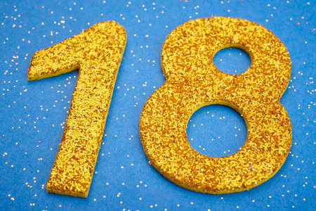 eighteen: Number eighteen yellow color over a blue background. Anniversary. Horizontal Stock Photo