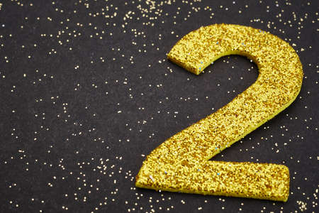 Number two golden color over a black background. Anniversary. Horizontal
