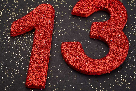 thirteen: Number thirteen red color over a black background. Anniversary. Horizontal